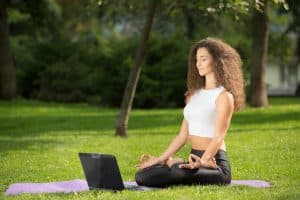 Meditating woman with laptop