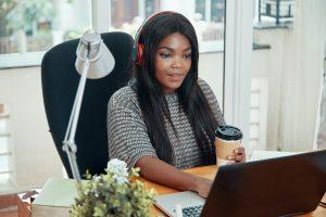 Black woman in headphones working on laptop