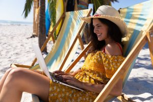 Caucasian woman sitting on a deck chair and using a laptop at the beach