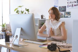 Front view of young Caucasian graphic designer with hand clasped doing yoga in creative office
