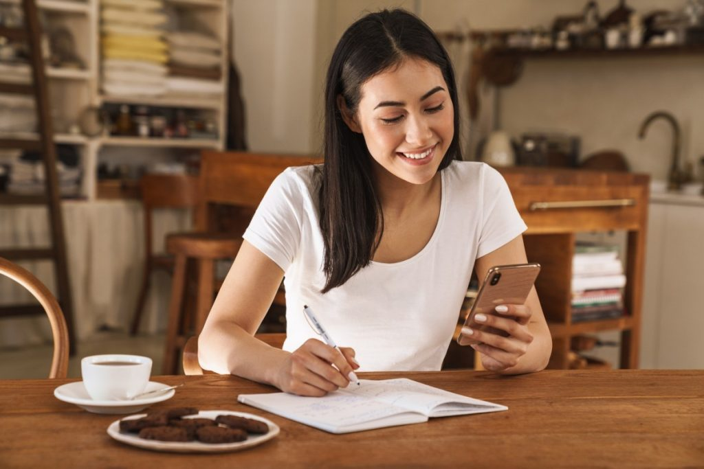 Image of smiling woman making notes in planner and using mobile phone