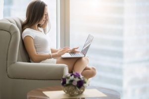 Young woman sitting in armchair with laptop