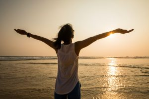 Woman feel free outstretched arms to sunset at seaside