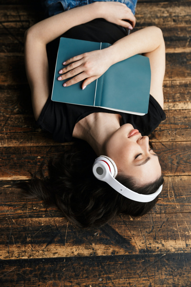 Photo of young woman wearing headphones lying on wooden floor with book