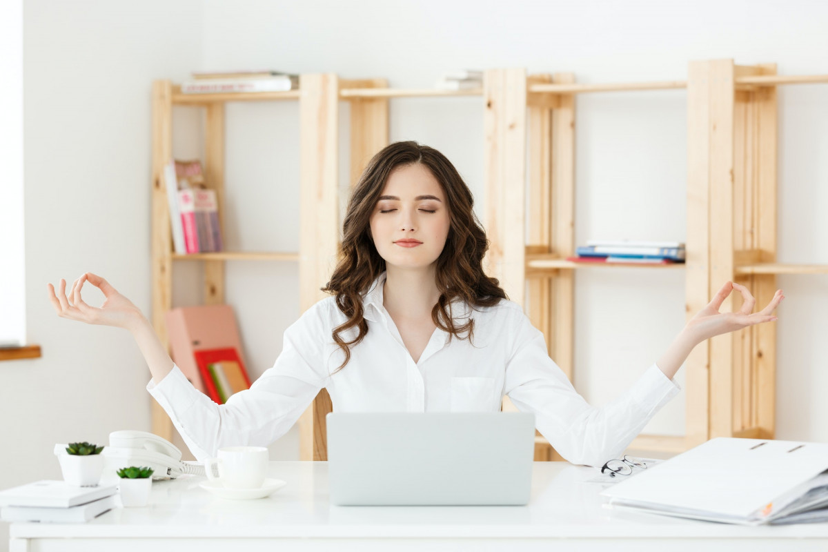Business and Health Concept: Portrait young woman near the laptop, practicing meditation at the