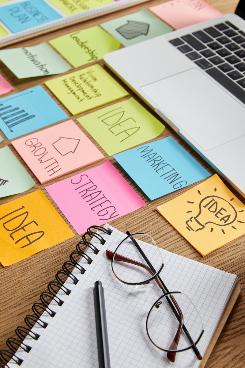 paper stickers with business strategy, laptop and notebook with pencil on tabletop