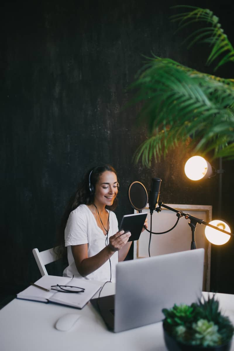 Young woman blogger recording podcast using microphone, tablet and laptop in a studio.