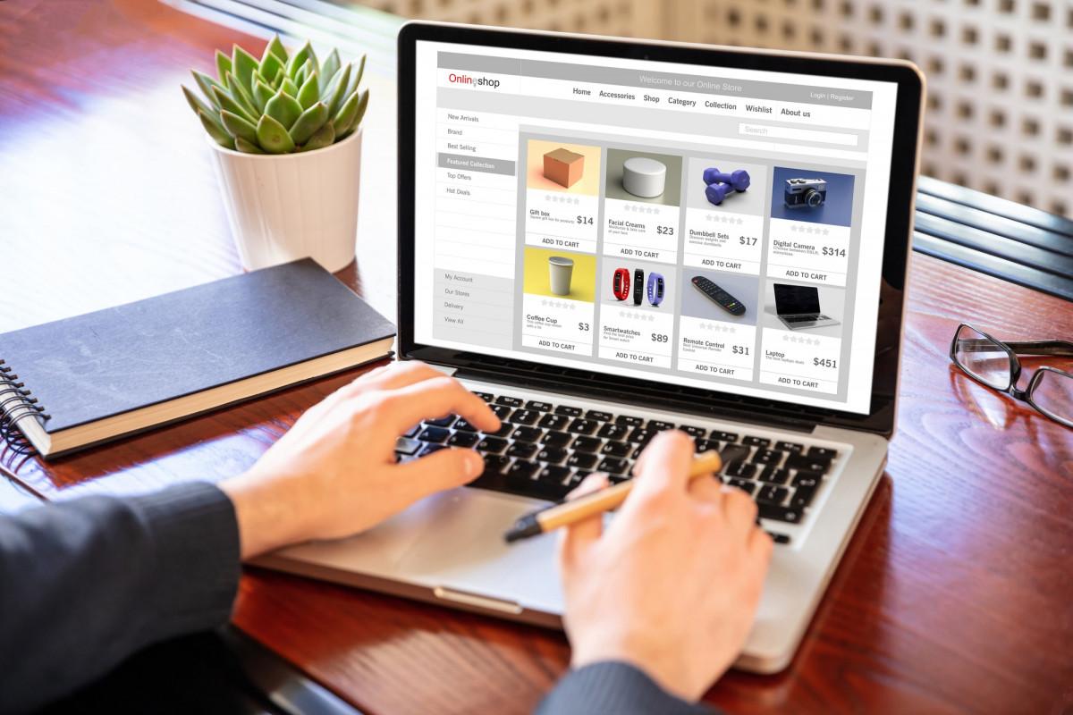 Online shop website developer working with a laptop, office desk background.