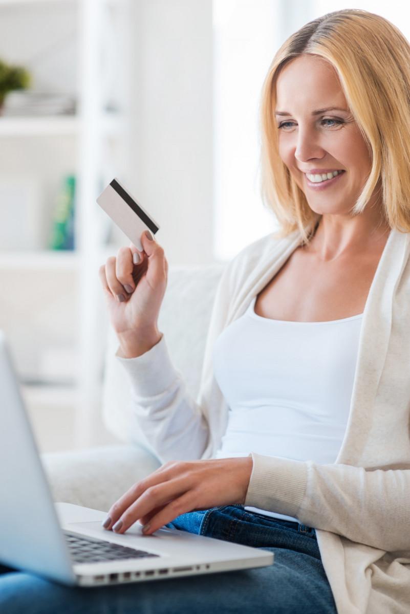 Shopping online. Smiling mature woman shopping through Internet while sitting on sofa