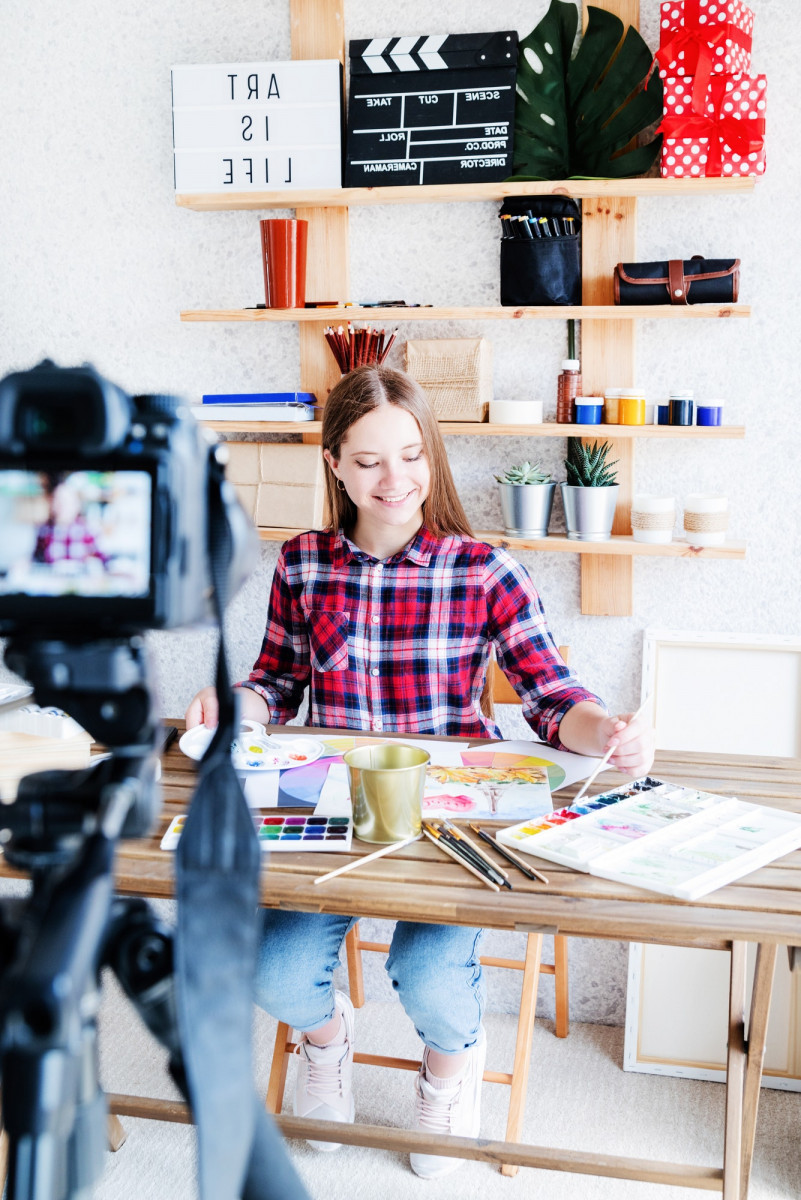 Smiling young woman drawing and recording video for her blog, teaching online, enjoying her hobby