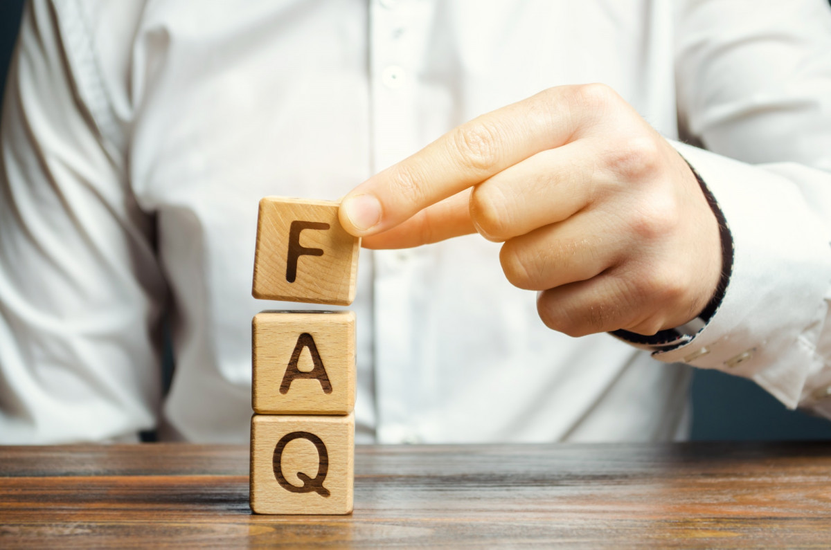 Businessman puts wooden blocks with the word FAQ (frequently asked questions)