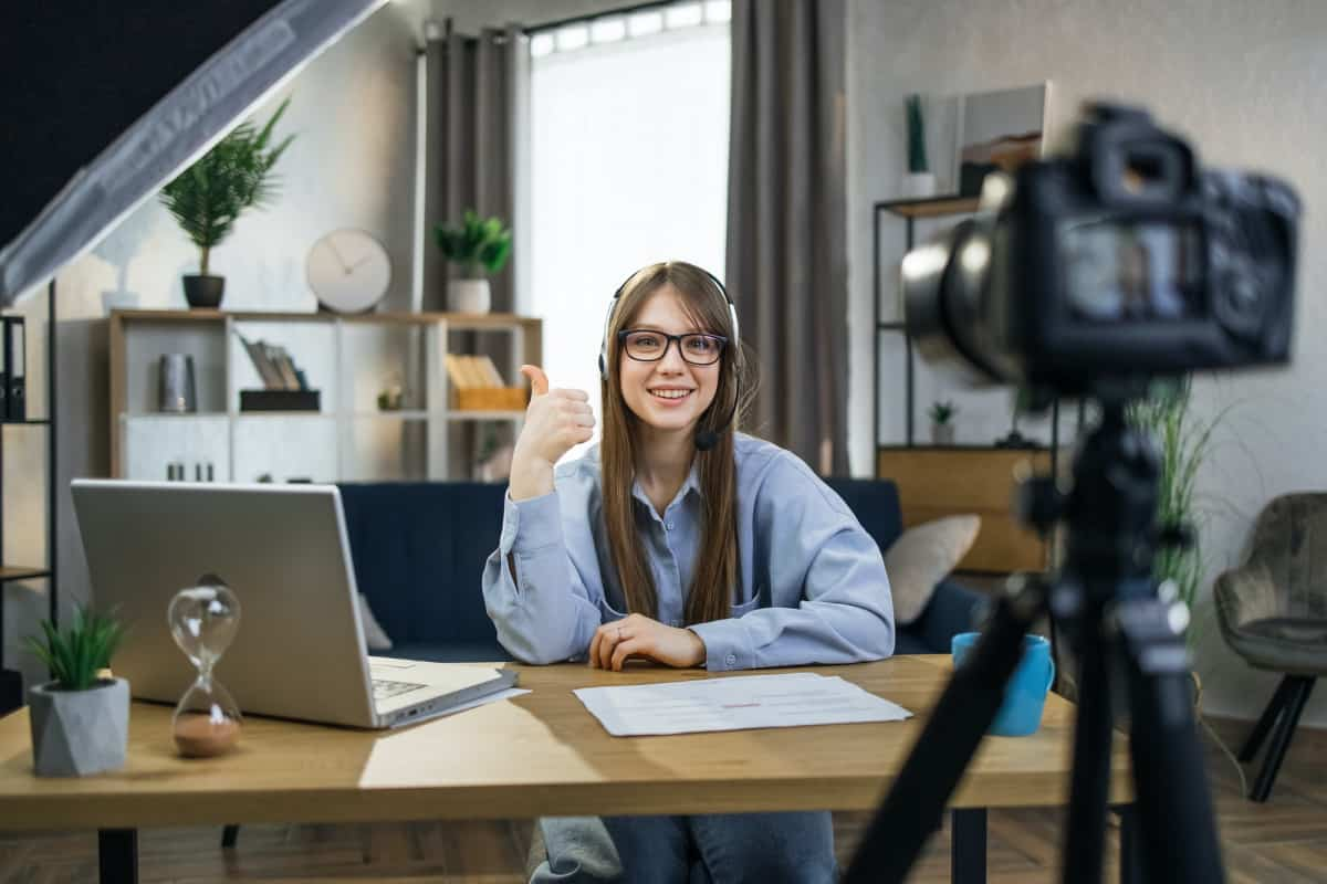 Woman in headset showing thumb up while filming video